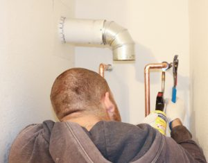 Josh Fisher soldering copper pipes for water heater